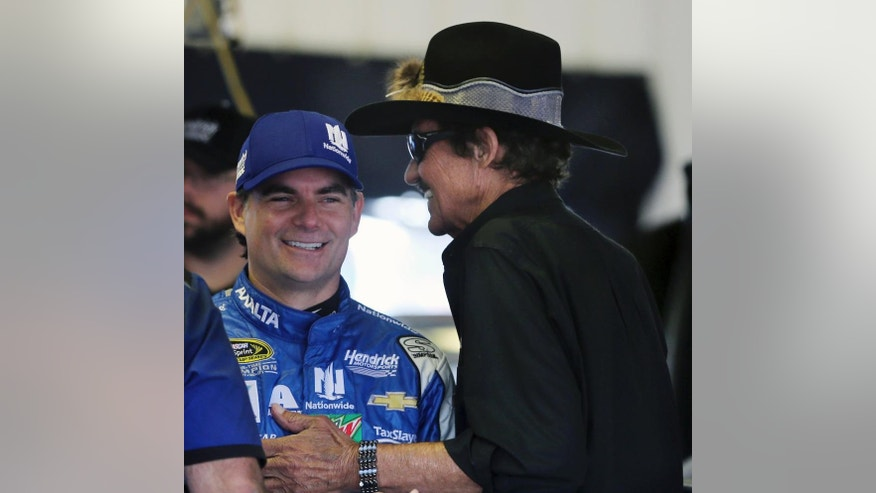 Racing legend Richard Petty, right, talks with Jeff Gordon (88) in the garage area at Pocono Raceway during practice for Sunday's NASCAR Sprint Cup Series Pennsylvania 400 auto race Sunday Friday, July 29, 2016, in Long Pond, Pa. Gordon came out of retirement to fill in for the injured Dale Earnhardt Jr. (AP Photo/Mel Evans)