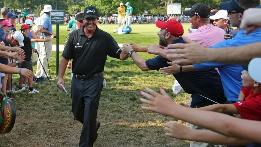 Phil Mickelson greets fans as he walks to the 12th tee during the second round of the PGA Championship golf tournament at Baltusrol Golf Club in Springfield, N.J., Friday, July 29, 2016. (AP Photo/Seth Wenig)