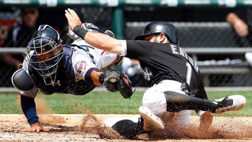 Thursday, June 30, 2016: Minnesota Twins catcher Kurt Suzuki dives to make the tag as the Chicago White Sox's Adam Eaton slides safely into home to score on a single by Jose Abreu during the third inning in Chicago. The Twins lost 6-5.