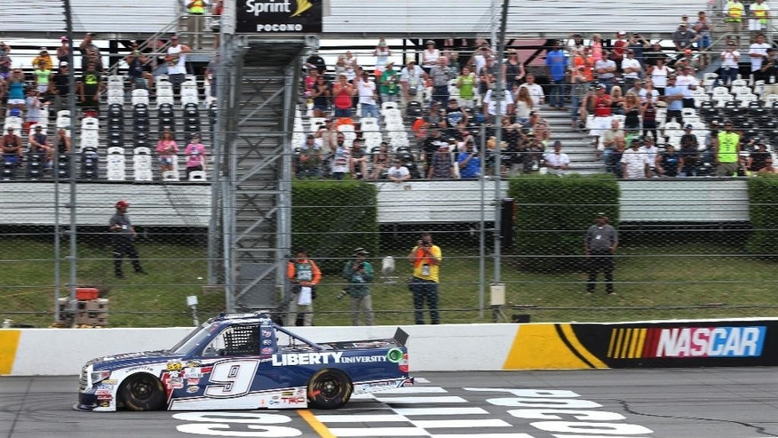 William Bryon (9) takes the checkered flag as he crosses the finish line to win the NASCAR truck series Pocono Mountains 150 auto race, Saturday, July 30, 2016, in Long Pond, Pa. (AP Photo/Mel Evans)