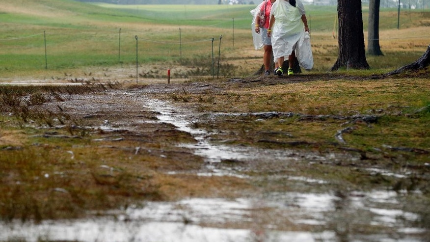 Women walk by the 18th hole after third round play was suspend for the day at the PGA Championship golf tournament at Baltusrol Golf Club in Springfield, N.J., Saturday, July 30, 2016. (AP Photo/Tony Gutierrez)
