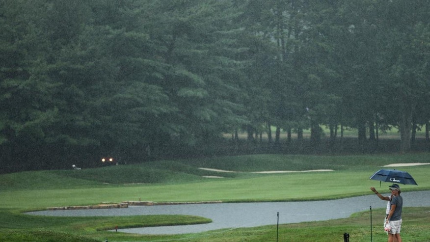 A couple look over the 18th fairway during a weather delay in the third round of the PGA Championship golf tournament at Baltusrol Golf Club in Springfield, N.J., Saturday, July 30, 2016. (AP Photo/Seth Wenig)