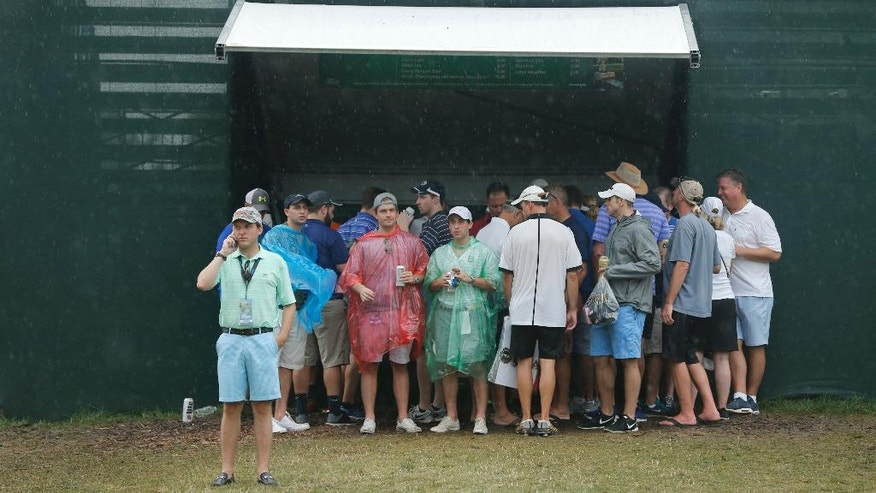 Fans take cover at the 18th green during a weather delay in the third round of the PGA Championship golf tournament at Baltusrol Golf Club in Springfield, N.J., Saturday, July 30, 2016. (AP Photo/Mike Groll)