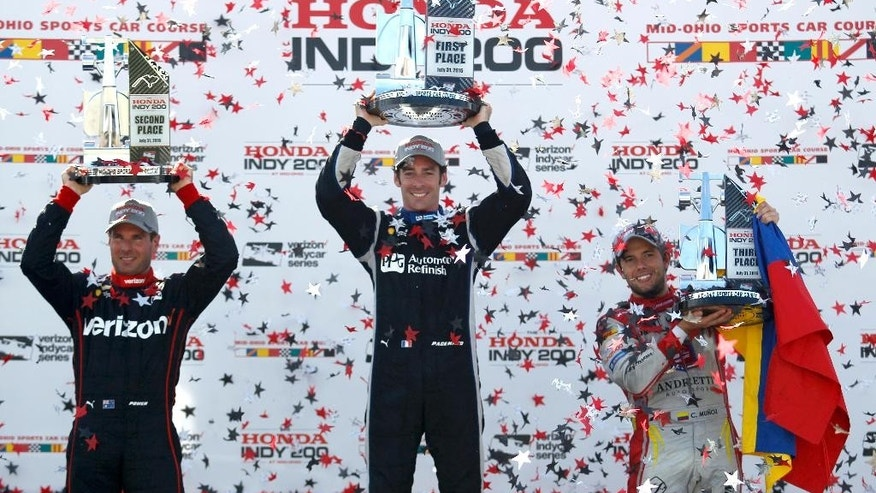 Winner Simon Pagenaud, of France, center, raises his trophy along with second-place finisher Will Power, left, of Australia, and third-place Carlos Munoz, of Colombia, at the IndyCar Honda Indy 200 auto race Sunday, July 31, 2016, at Mid-Ohio Sports Car Course in Lexington, Ohio. (AP Photo/Tom E. Puskar)