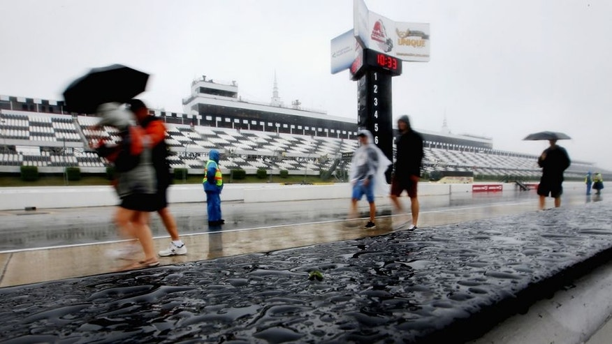 LONG POND, PA - JULY 31: Race fans walk down pit road in the rain prior to the NASCAR Sprint Cup Series Pennsylvania 400 at Pocono Raceway on July 31, 2016 in Long Pond, Pennsylvania. (Photo by Sean Gardner/Getty Images)