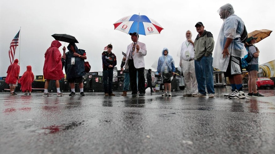 NASCAR fans take a tour in the rain of the garage area at Pocono Raceway before the NASCAR Sprint Cup Series Pennsylvania 400 auto race Sunday, July 31, 2016, in Long Pond, Pa. (AP Photo/Mel Evans)