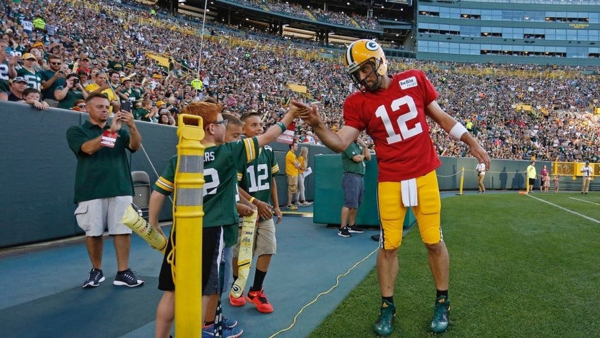 <p>Green Bay Packers quarterback Aaron Rodgers high fives a fan on the sidelines during training camp, Sunday, July 31.</p>