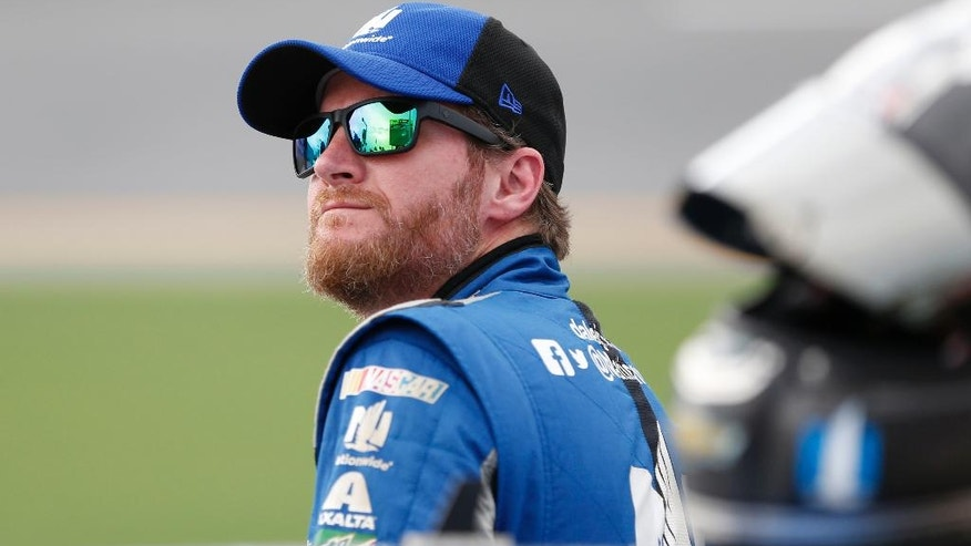 File-This July 1, 2016, file photo shows Dale Earnhardt Jr. watching the leader-board during qualifying for a NASCAR Sprint Cup auto race at Daytona International Speedway in Daytona Beach, Fla. Earnhardt Jr. says his concussion-like symptoms haven't changed and his return to NASCAR doesn't appear imminent. NASCAR's most popular driver is scheduled to miss his third consecutive race Sunday because he suffers from symptoms of a concussion. Earnhardt tweeted Saturday, July 30, 2016, there was no change in his condition.  (AP Photo/Wilfredo Lee, File)