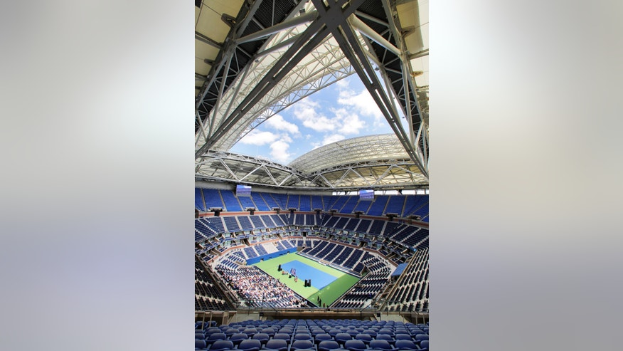 The partially open new retractable roof allows light into Arthur Ashe Stadium at the Billie Jean King National Tennis Center, in the Queens borough of New York, Tuesday, Aug. 2, 2016. Mother Nature will no longer be a problem at the U.S. Open as the U.S. Tennis Association unveiled the new retractable roof over Arthur Ashe Stadium. (AP Photo/Richard Drew)