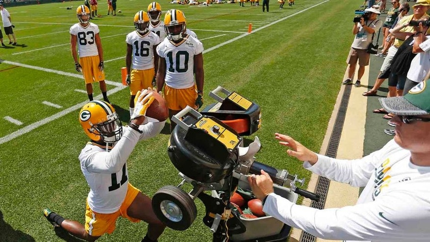 <p>Green Bay Packers wide receiver Davante Adams catches a pass while wide receivers Jamel Johnson, Herb Waters, Jeff Janisand Randall Cobb watch during training camp onTuesday, July 26,at Ray Nitschke Field.</p>