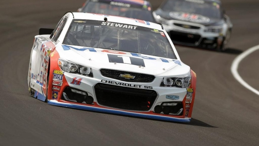 FILE - In this July 24, 2016, file photo, Tony Stewart (14) drives through the first turn during the Brickyard 400 NASCAR auto race at Indianapolis Motor Speedway in Indianapolis. Stewart will get a throwback paint scheme for the Southern 500, his final race at Darlington. (AP Photo/Michael Conroy, File)
