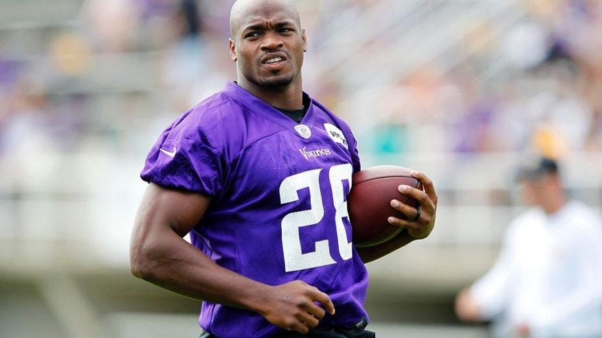 <p>Minnesota Vikings running back Adrian Peterson runs with the ball during the first day of training camp at Mankato State University in Mankato.</p>