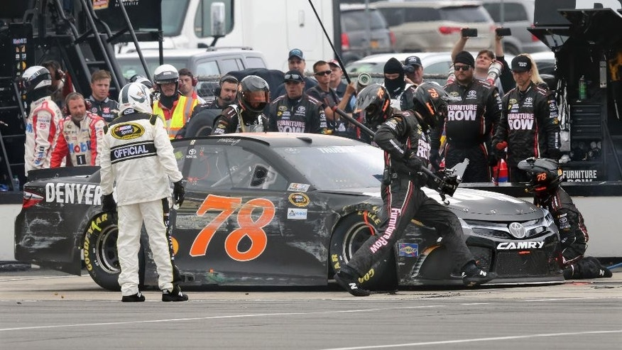 Crew members work on the damaged race car of Martin Truex Jr. (78) in the pits during the NASCAR Sprint Cup Series Pennsylvania 400 auto race at Pocono Raceway, Monday, Aug. 1, 2016, in Long Pond, Pa. (AP Photo/Mel Evans)