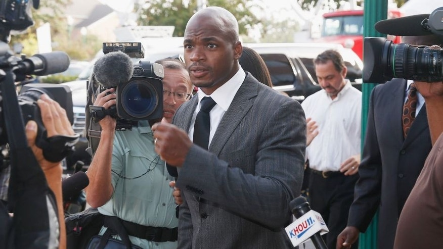 CONROE, TX - OCTOBER 08: NFL player Adrian Peterson of the Minnesota Vikings walks to a court appearance at the Montgomery County municipal building on October 8, 2014 in Conroe, Texas. Peterson did not enter a plea, and after about an hour in the courtroom the hearing was reset. A tentative trial date was set for Dec. 1. Petersen is facing charges of reckless or negligent injury to a child. (Photo by Scott Halleran/Getty Images)