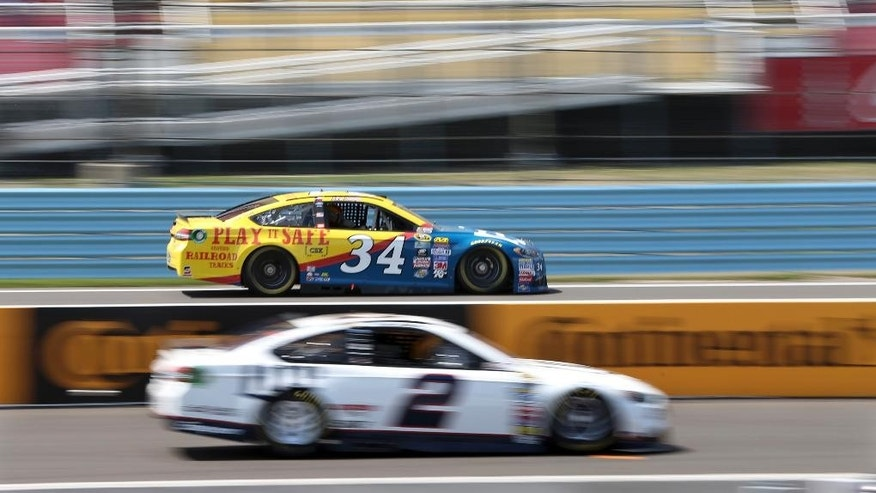 Chris Buescher (34) drives past the pits and Brad Keselowski (2) during practice at Watkins Glen International race track for Sunday's NASCAR Sprint Cup Series Cheez-It 355 auto race Friday, Aug. 5, 2016, in Watkins Glen, N.Y. (AP Photo/Mel Evans)