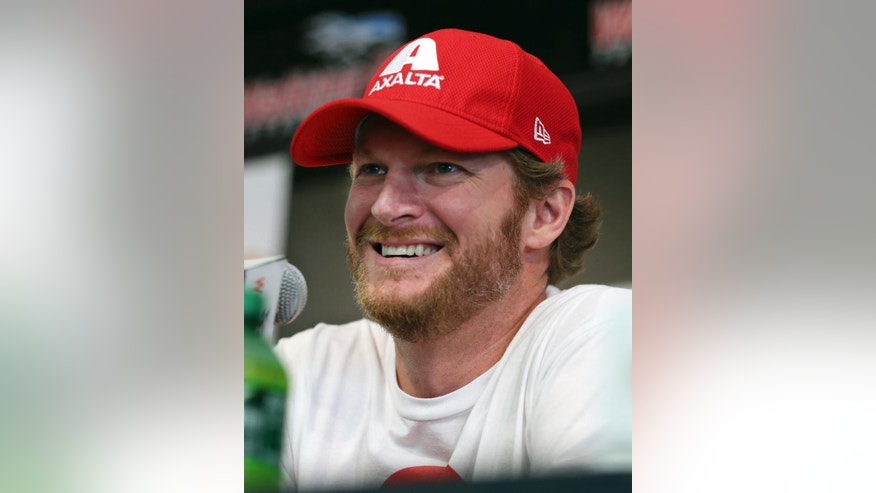 Dale Earnhardt Jr. smiles as he listens to a question about his concussion while addressing the media at Watkins Glen International racetrack during practice for Sunday's NASCAR Sprint Cup Series auto race Friday, Aug. 5, 2016, in Watkins Glen, N.Y. Jeff Gordon came out of retirement to fill in for the injured Dale Earnhardt Jr. (AP Photo/Mel Evans)