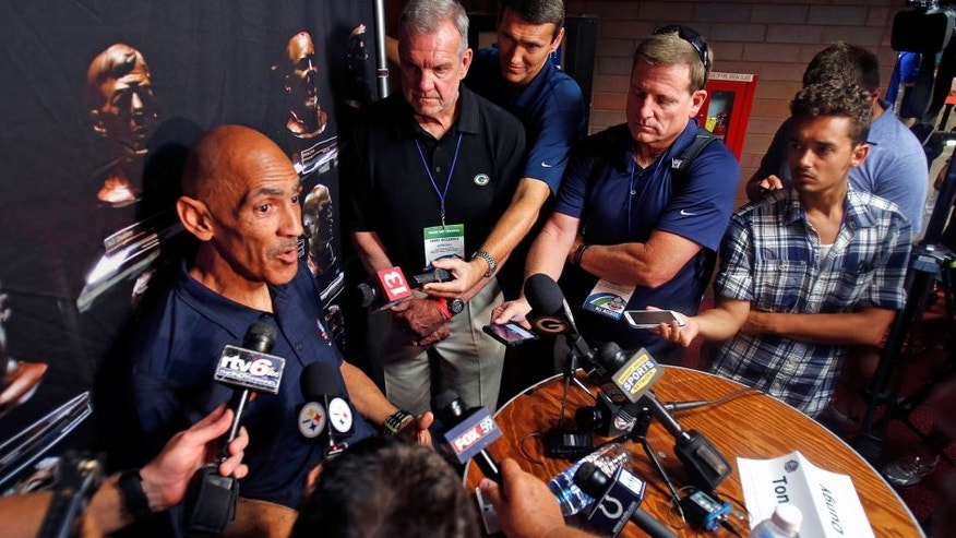 Pro Football Hall of Fame 2016 inductee Tony Dungy, left, talks with reporters Friday, Aug. 5, 2016, in Canton, Ohio. (AP Photo/Gene J. Puskar)