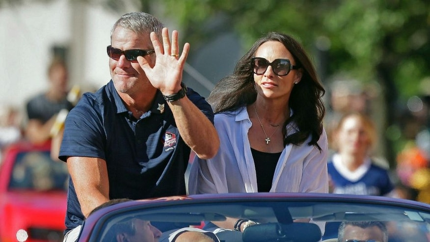 Aug 6, 2016; Canton, OH, USA; Hall of Fame inductee Brett Favre and his wife Deanna Favre wave to the crowd along the parade route during the Canton Repository Grand Parade as part of the NFL Pro Football Hall of Fame Enshrinement Festival. Mandatory Credit: Rick Wood/Milwaukee Journal Sentinel via USA TODAY Network