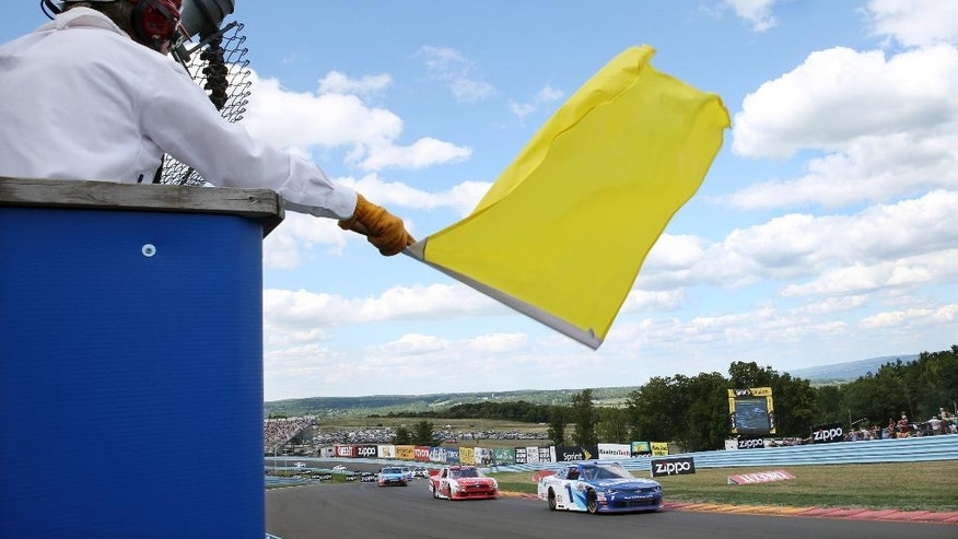 A track marshall waves a yellow caution flag during an NASCAR Xfinity series auto race at Watkins Glen International, Saturday, Aug. 6, 2016, in Watkins Glen, N.Y. (AP Photo/Mel Evans)