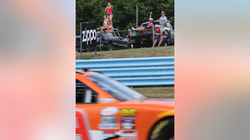 Fans point and cheer during an NASCAR Xfinity series auto race at Watkins Glen International race track, Saturday, Aug. 6, 2016, in Watkins Glen, N.Y. (AP Photo/Mel Evans)