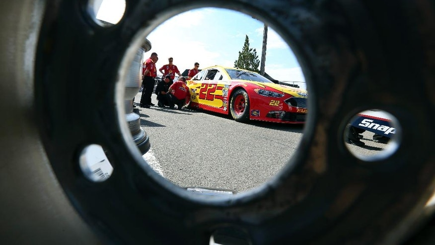 The race car of Joey Logano (22) is seen through a race wheel in the garage area at Watkins Glen International racetrack during practice for Sunday's NASCAR Sprint Cup Series auto race Friday, Aug. 5, 2016, in Watkins Glen, N.Y. (AP Photo/Mel Evans)