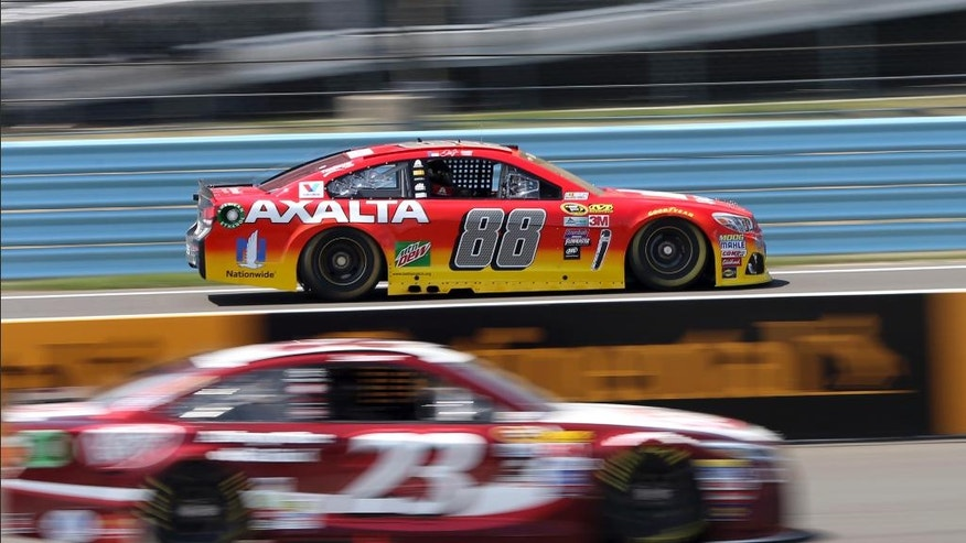 Jeff Gordon (88) drives past the pits and David Ragan (23) at Watkins Glen International racetrack during practice for Sunday's NASCAR Sprint Cup Series auto race Friday, Aug. 5, 2016, in Watkins Glen, N.Y. Gordon came out of retirement to fill in for the injured Dale Earnhardt Jr. (AP Photo/Mel Evans)