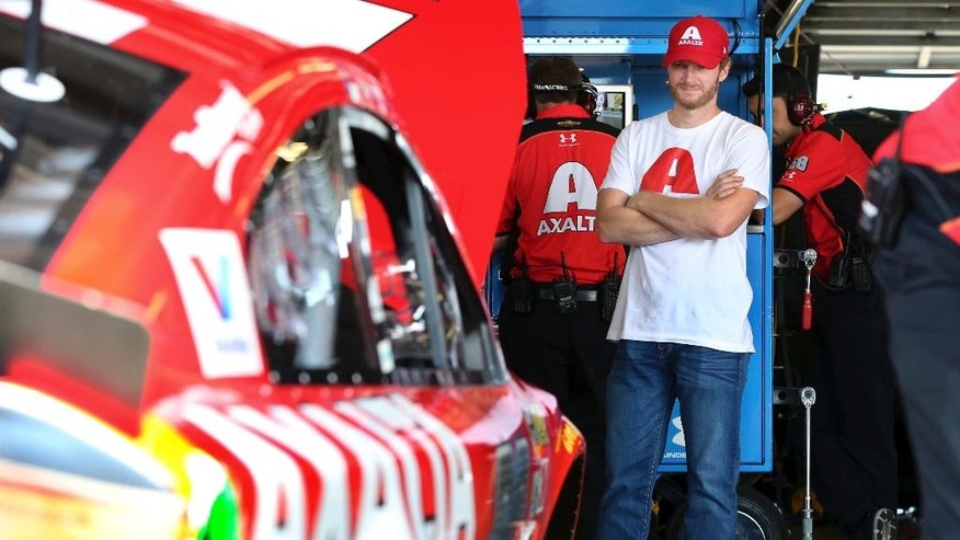Dale Earnhardt Jr., who is recuperating from a concussion, looks a his race car in the garage area at Watkins Glen International racetrack during practice for Sunday's NASCAR Sprint Cup Series auto race Friday, Aug. 5, 2016, in Watkins Glen, N.Y. Jeff Gordon came out of retirement to fill in for the injured Dale Earnhardt Jr. (AP Photo/Mel Evans)