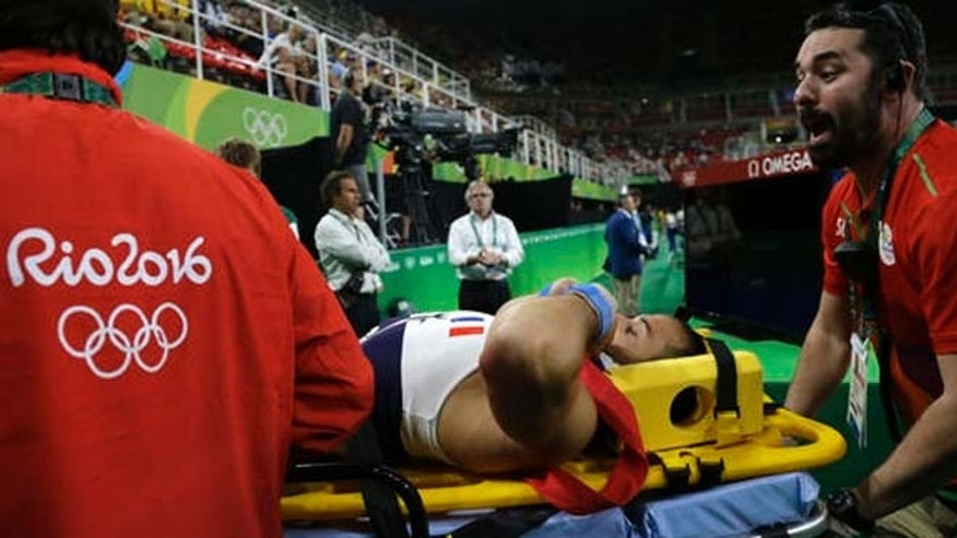France's Samir Ait Said is carried away on a stretcher after he injured himself while performing on the vault during the artistic gymnastics men's qualification at the 2016 Summer Olympics Saturday.