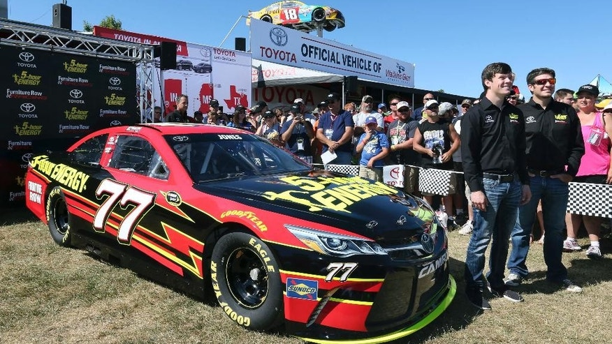 Erik Jones stands with his new racing Toyota Camry (77) and his Furniture Row Racing teammate Martin Truex Jr., right, during his introduction at Watkins Glen International race track before a NASCAR Sprint Cup Series auto race Sunday, Aug. 7, 2016, in Watkins Glen, N.Y. (AP Photo/Mel Evans)