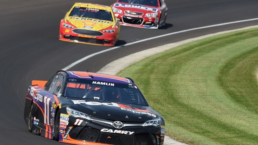 INDIANAPOLIS, IN - JULY 24: Denny Hamlin, driver of the #11 FedEx Express Toyota, leads Joey Logano, driver of the #22 Shell Pennzoil Ford, and Jimmie Johnson, driver of the #48 Lowe's Red Vest Chevrolet, during the NASCAR Sprint Cup Series Crown Royal Presents the Combat Wounded Coalition 400 at Indianapolis Motor Speedway on July 24, 2016 in Indianapolis, Indiana. (Photo by Bobby Ellis/Getty Images)