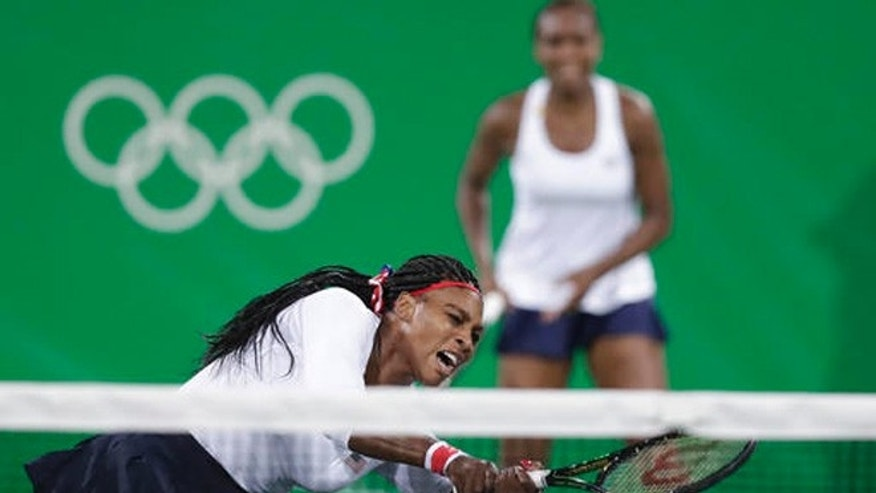 Serena Williams, of the United States, reacts after losing a point at the net in a doubles match with her sister Venus, rear, against Lucie Sarfarova and Barbora Strycova, of the Czech Republic, at the 2016 Summer Olympics in Rio de Janeiro, Brazil, Sunday, Aug. 7, 2016.