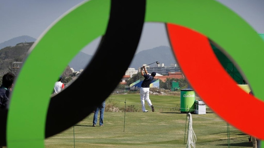 Brazil's Adilson Da Silva, center, hits off the first tee during golf practice at the 2016 Summer Olympics in Rio de Janeiro, Brazil, Friday, Aug. 5, 2016. (AP Photo/Charlie Neibergall)
