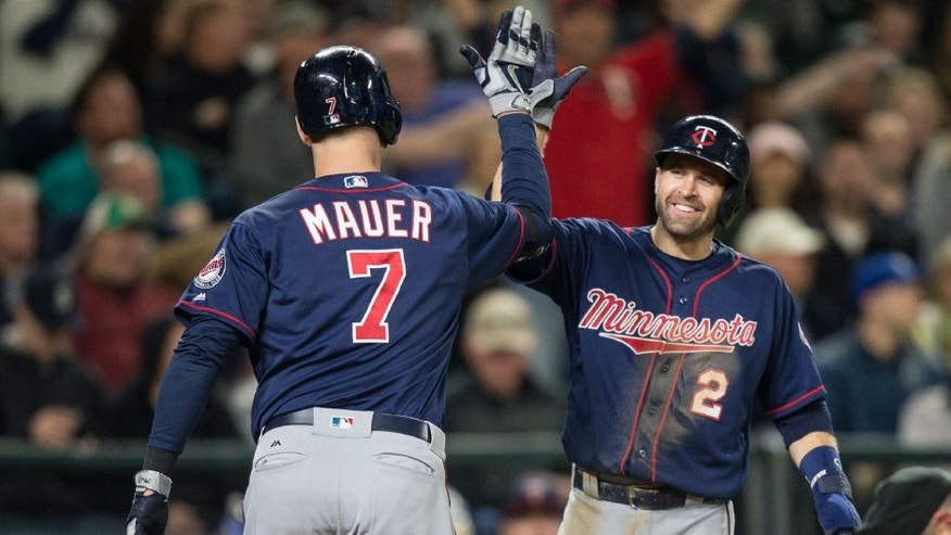 Minnesota Twins' Brian Dozier, right, congratulates Joe Mauer after Mauer hit a two-run home run that scored Dozier during the fifth inning of a baseball game against the Seattle Mariners.