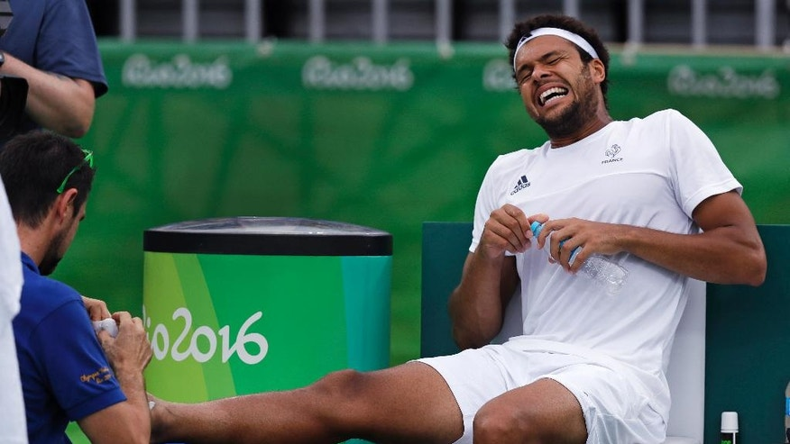 Jo-Wilfried Tsonga, of France, winces in pain as a trainer attends to his injured right foot during a match against Gilles Muller, of Luxembourg, at the 2016 Summer Olympics in Rio de Janeiro, Brazil, Monday, Aug. 8, 2016. (AP Photo/Charles Krupa)