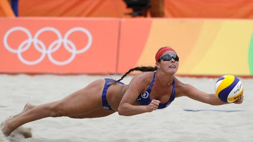 Unites States' Brooke Sweat dives for the ball against Poland during a women's beach volleyball match at the 2016 Summer Olympics in Rio de Janeiro, Brazil, Sunday, Aug. 7, 2016.