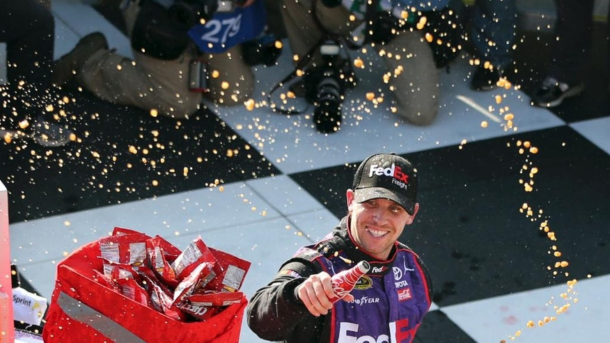 Denny Hamlin (11) celebrates in Victory Lane after winning a NASCAR Sprint Cup Series auto race at Watkins Glen International, Sunday, Aug. 7, 2016, in Watkins Glen, N.Y. (AP Photo/Mel Evans)