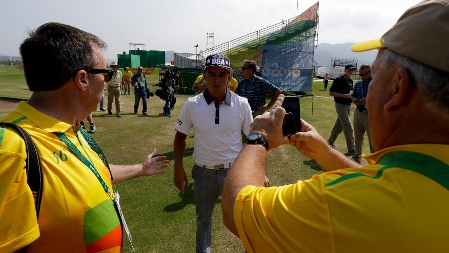 Volunteers greets Rickie Fowler, of the, United States, after a practice round for men's golf event at the 2016 Summer Olympics in Rio de Janeiro, Brazil, Tuesday, Aug. 9, 2016. (AP Photo/Chris Carlson)
