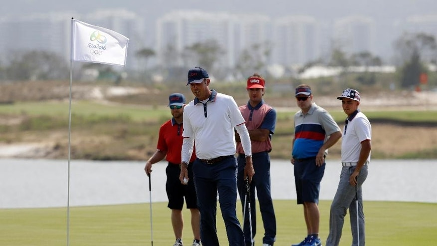Matt Kuchar, of the United States,reacts to his putt on the third green, watched by Bubba Watson, of the United States, centre, and Rickie Fowler, of the United States, right, during a practice round for the men's golf event at the 2016 Summer Olympics in Rio de Janeiro, Brazil, Tuesday, Aug. 9, 2016. (AP Photo/Alastair Grant)