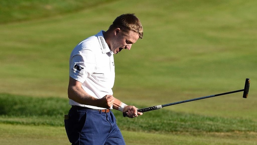 Russell Knox, from Scotland, celebrates after his winning putt on the 18th hole during the final round of the Travelers Championship golf tournament in Cromwell, Conn., Sunday, Aug. 7, 2016. (AP Photo/Fred Beckham)