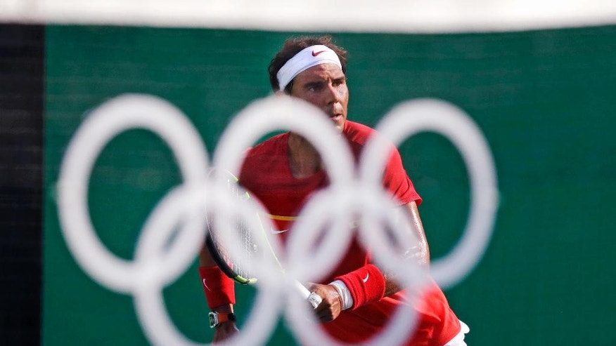 Rafael Nadal, of Spain, seen through the Olympic rings on the net as center court, returns to Andreas Seppi, of Italy, at the 2016 Summer Olympics in Rio de Janeiro, Brazil, Tuesday, Aug. 9, 2016. (AP Photo/Charles Krupa)