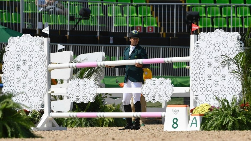 Brazil's Ruy Fonseca replaces the bar after he fell from his horse Tom Bombadill Too while competing during the Eventing's Individual Jumping of the Equestrian during the 2016 Rio Olympic Games at the Olympic Equestrian Centre in Rio on August 9, 2016. / AFP / John MACDOUGALL (Photo credit should read JOHN MACDOUGALL/AFP/Getty Images)