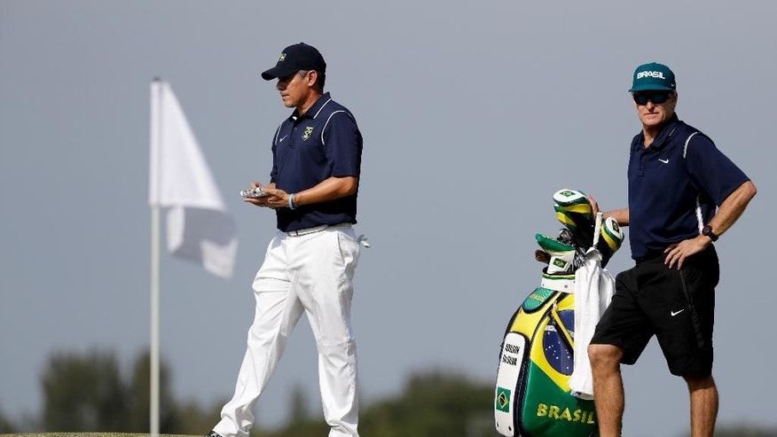 Adilson da Silva, of Brazil, left, walks around the ninth green with his caddie, Andrew Edmondson during a practice round for men's golf event at the 2016 Summer Olympics in Rio de Janeiro, Brazil, Tuesday, Aug. 9, 2016. Da Silva was 11, when he first caddied for Edmondson, a tobacco buyer who spent half his year in Brazil. Edmondson later brought him to Zimbabwe because of a strong junior golf program. Now that Da Silva is in the Olympics, Edmondson will caddie for him. (AP Photo/Chris Carlson)