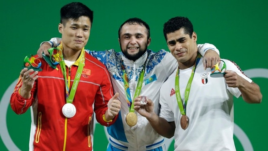 Gold medalist Nijat Rahimov, of Kazakhstan, center, stands with silver medalist Lyu Xiaojun, of China, left, and bronze medalist Mohamed Mahmoud, of Egypt, right, after the men's 77kg weightlifting competition at the 2016 Summer Olympics in Rio de Janeiro, Brazil, Wednesday, Aug. 10, 2016.