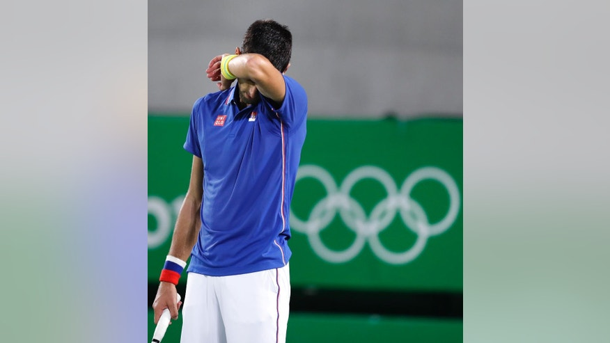 Novak Djokovic, of Serbia, reacts while trailing in a second set tie breaker against Juan Martin del Potro, of Argentina, at the 2016 Summer Olympics in Rio de Janeiro, Brazil, Sunday, Aug. 7, 2016. (AP Photo/Charles Krupa)