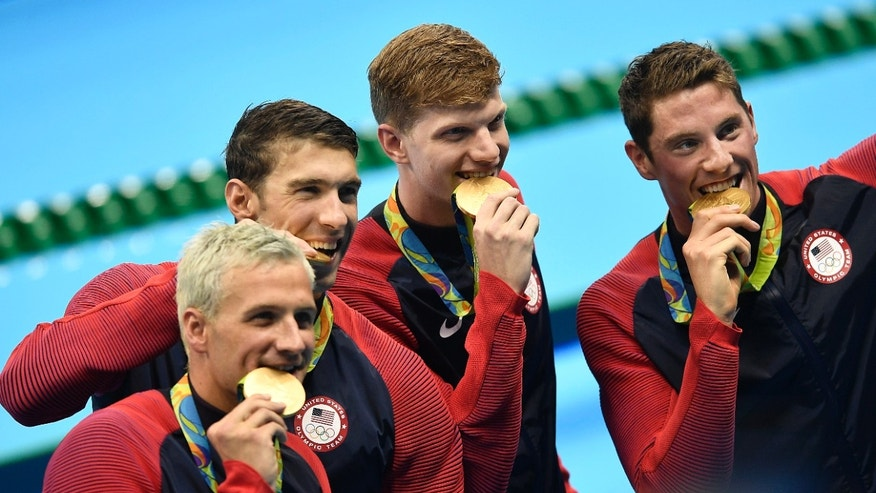 From left, Ryan Lochte, Michael Phelps, Towny Haas and Conor Dwyer from the United States bite their gold medals after the ceremony for the men's 4x200-meter freestyle final.