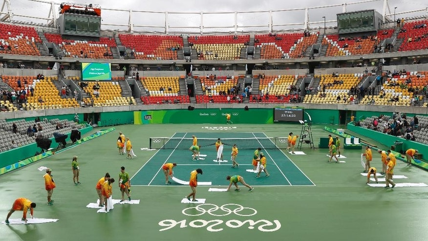Volunteers use towels to dry the field of play on the central tennis court following a rainfall that delayed matches in the tennis competition at the 2016 Summer Olympics in Rio de Janeiro, Brazil, Wednesday, Aug. 10, 2016. (AP Photo/Vadim Ghirda)