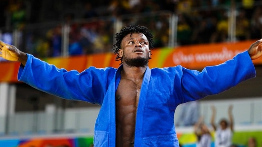 Popole Misenga, who competes for the Refugee Olympic Team, reacts after winning his first match against India's Avtar Singh during the men's 90-kg judo competition at the 2016 Summer Olympics in Rio de Janeiro, Brazil, Wednesday, Aug. 10, 2016.