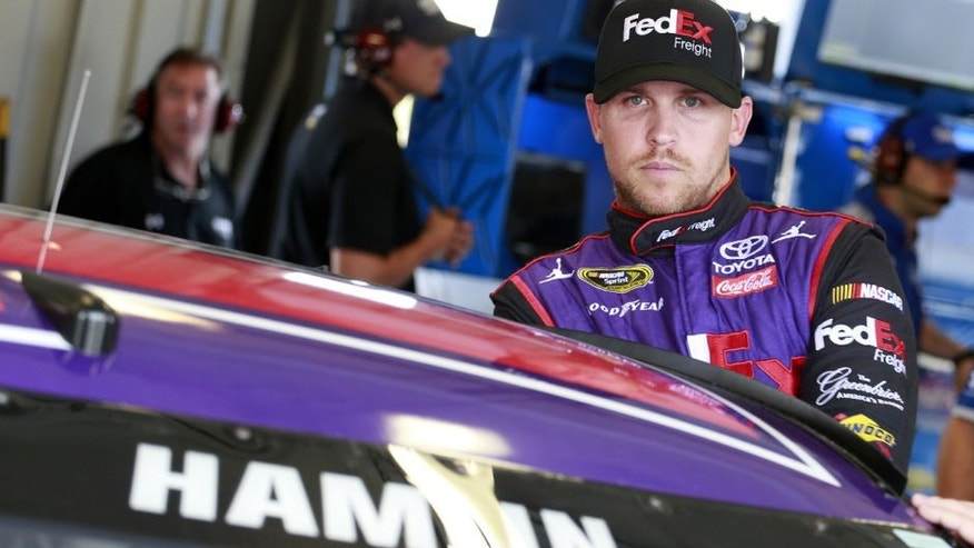 SPARTA, KY - JULY 07: Denny Hamlin, driver of the #11 FedEx Freight Toyota, stands in the garage area during practice for the NASCAR Sprint Cup Series Quaker State 400 at Kentucky Speedway on July 7, 2016 in Sparta, Kentucky. (Photo by Matt Sullivan/Getty Images)