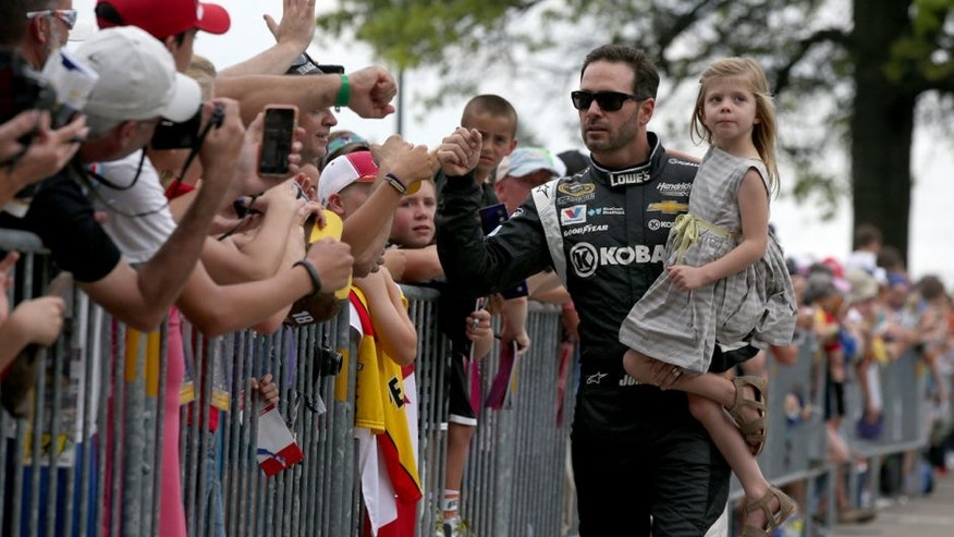 INDIANAPOLIS, IN - JULY 26: Jimmie Johnson, driver of the #48 Kobalt Tools Chevrolet, and his daughter Genevieve walk along The Yard of Bricks prior to being introduced for the NASCAR Sprint Cup Series Crown Royal Presents the Jeff Kyle 400 at the Brickyard at Indianapolis Motor Speedway on July 26, 2015 in Indianapolis, Indiana. (Photo by Sean Gardner/NASCAR via Getty Images)