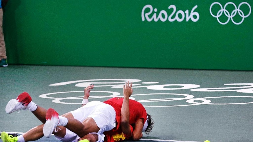 Rafael Nadal, of Spain, top, embraces partner Marc Lopez as they celebrate after defeating Canada in their men's doubles match at the 2016 Summer Olympics in Rio de Janeiro, Brazil, Thursday, Aug. 11, 2016. (AP Photo/Charles Krupa)